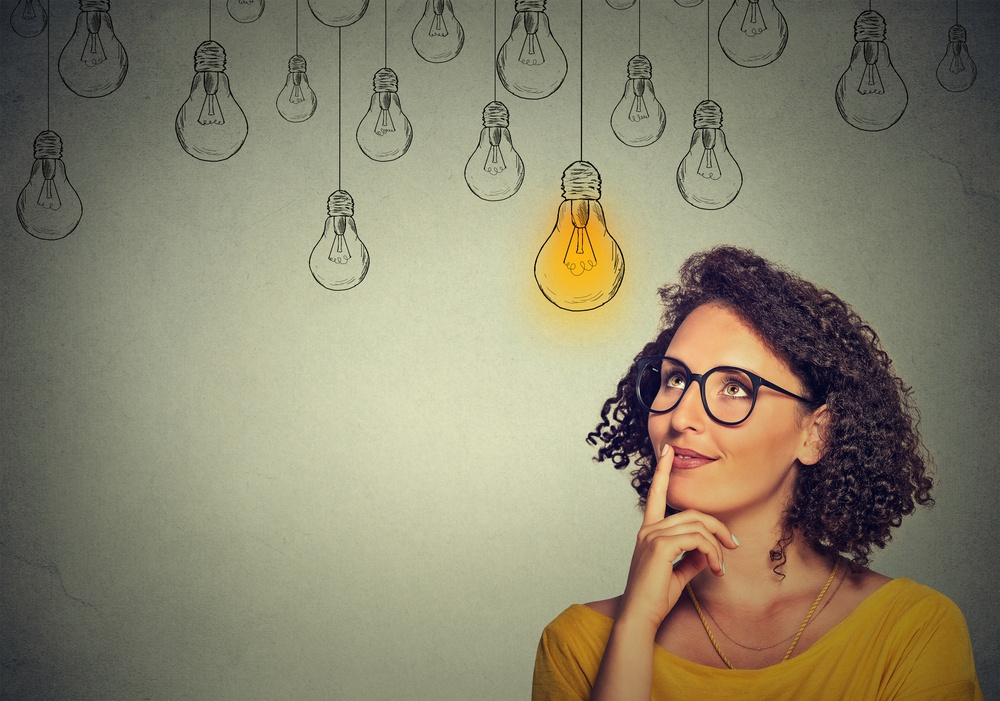 Thinking woman in glasses looking up with light idea bulb above head isolated on gray wall background